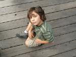 Ein kleiner Junge sitzt auf dem Boden und sieht nach oben.