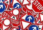 Unruhig wirkendes Bild mit verschiedenen Verkehrszeichen, beispielsweise Stoppschilder, Vorfahrt achten, Einfahrt verboten.