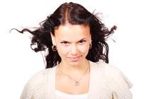 Jugendliches Mädchen blickt frontal mit wehenden Haaren zum Betrachter.