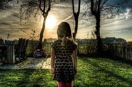 Ein kleines Mädchen steht alleine in einem umzeunten Garten und blickt in die Ferne.
