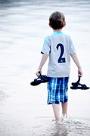 Ein kleiner Junge watet durch niedriges Wasser und trägt seine Sandalen.