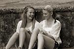 Zwei jugendliche Mädchen sitzen auf dem Boden. Ein Mädchen lacht, die andere schaut nachdenklich.