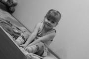 Kleines Mädchen sitzt in ihrem Bett und schaut schüchtern.