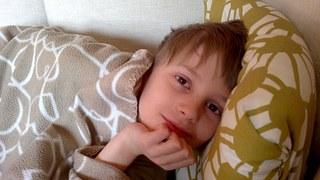 Etwa zehnjähriger Junge liegt im Bett und sieht in Richtung des Betrachters.