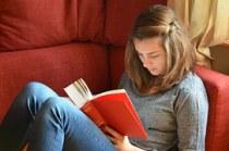 Foto eines Mädchens beim Lesen auf der Couch.