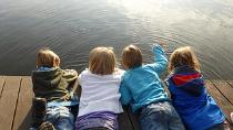 Vier Kinder liegen nahe beieinander bäuchlings auf einem Steg und schauen ins Wasser.