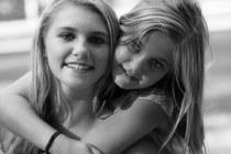Zwei befreundete jugendliche Mädchen blicken den Betrachter lächelnd an.