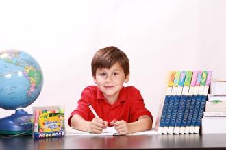 Ein Junge sitzt am Schreibtisch, auf dem sich verschiedenes Lernmaterial befindet.