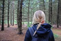 Bild eines Mädchens von hinten, das alleine im Wald steht.
