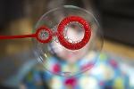 Bild einer Seifenblase hinter der verschwommen ein Kindergesicht zu sehen ist.