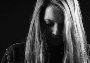Schwarz-weißes Porträt-Bild einer Frau, die nach unten schaut. Das Gesicht ist kaum zu erkennen.
