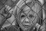 Bild eines Kindes, das hinter einem Maschendrahtzaun steht und traurig schaut.